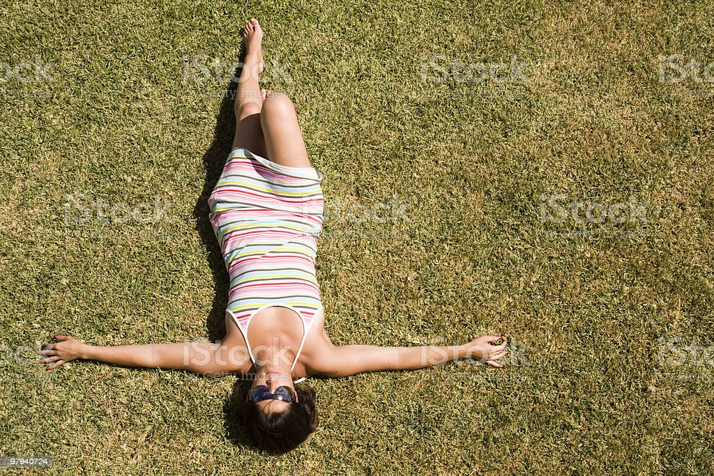 woman laying in the grass royalty-free stock photo