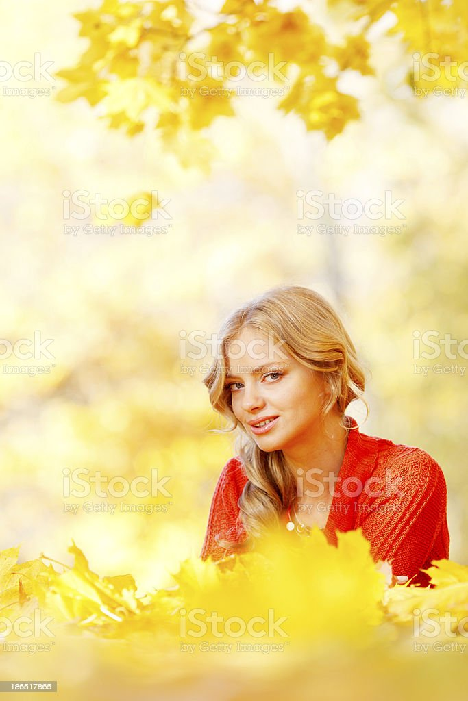 Woman laying on autumn leaves royalty-free stock photo