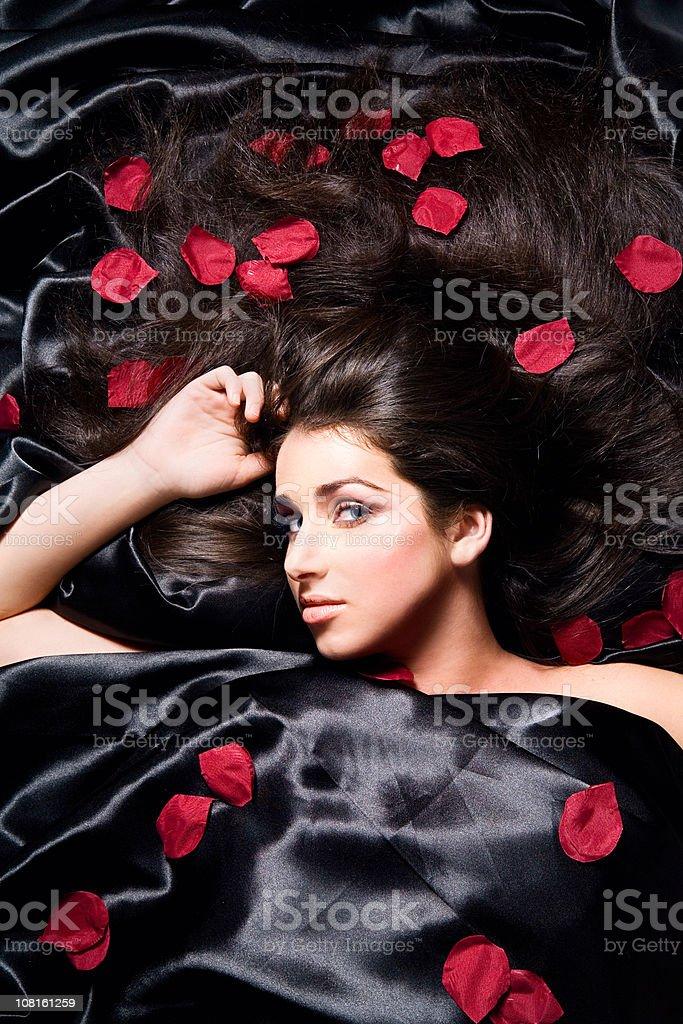 woman laying on black satin sheets with rose petals royaltyfree stock photo