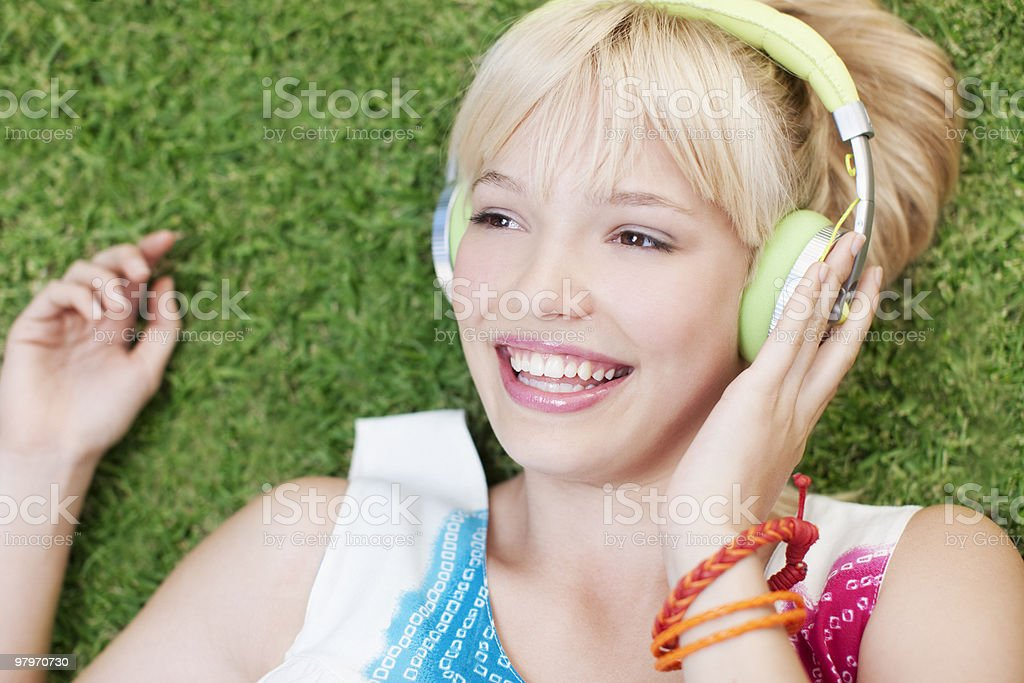 Woman laying on grass listening to headphones royalty-free stock photo
