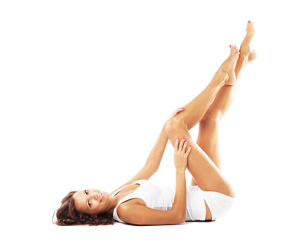 Woman laying on her back caressing her leg stock photo