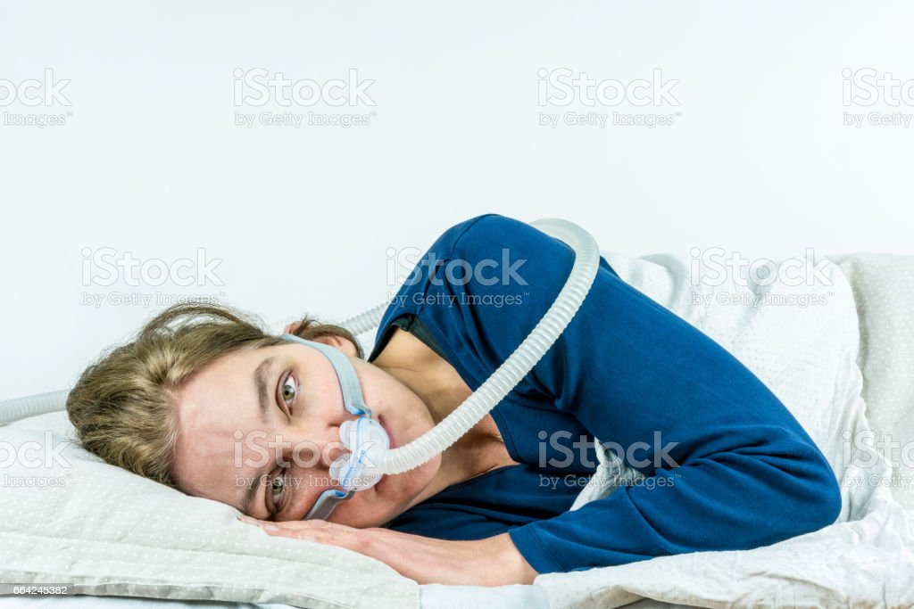 Woman laying on her side with eyes open looking in to camera. CPAP, sleep apnea treatment. Studio portrait white background. stock photo