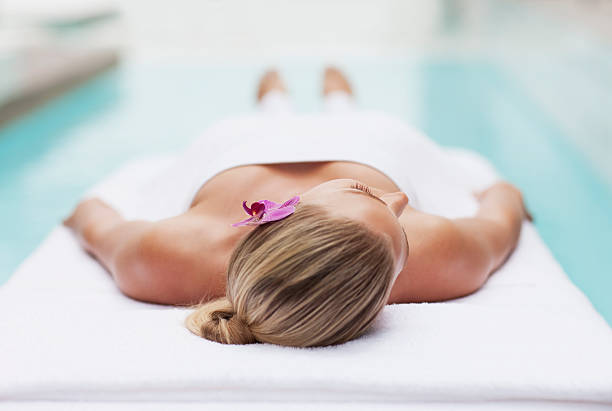 woman laying on massage table at poolside - spa treatment stock photos and pictures