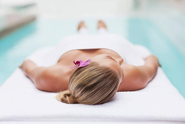 Femme jeter sur la table de massage au bord de la piscine - Photo