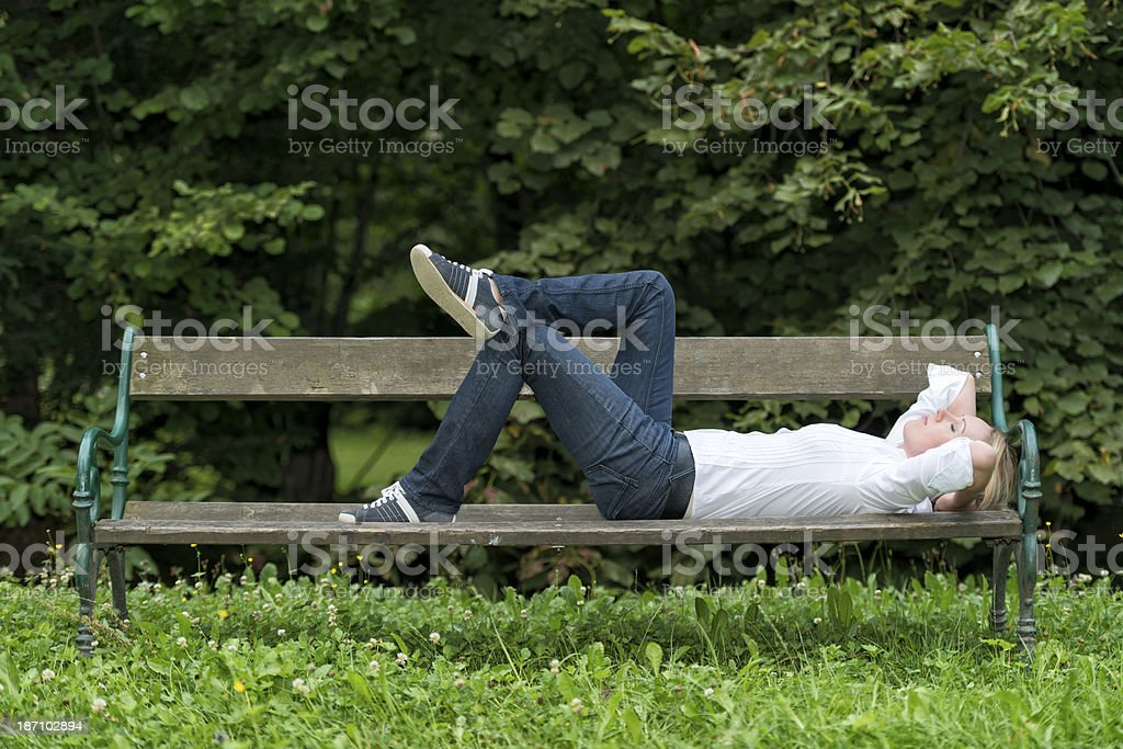 Woman laying on park bench sleeping in a park. royalty-free stock photo