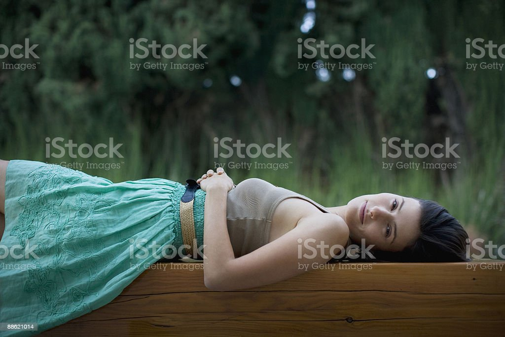 Woman laying on wooden bench royalty-free stock photo