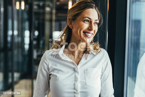 Young business woman looking through window