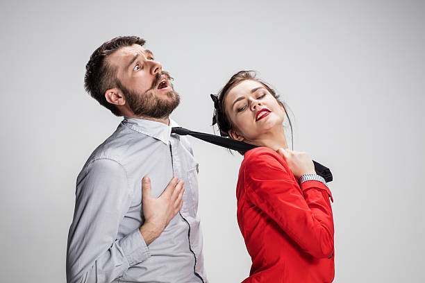 woman leading a man by his tie - man dominating woman stock photos and pictures
