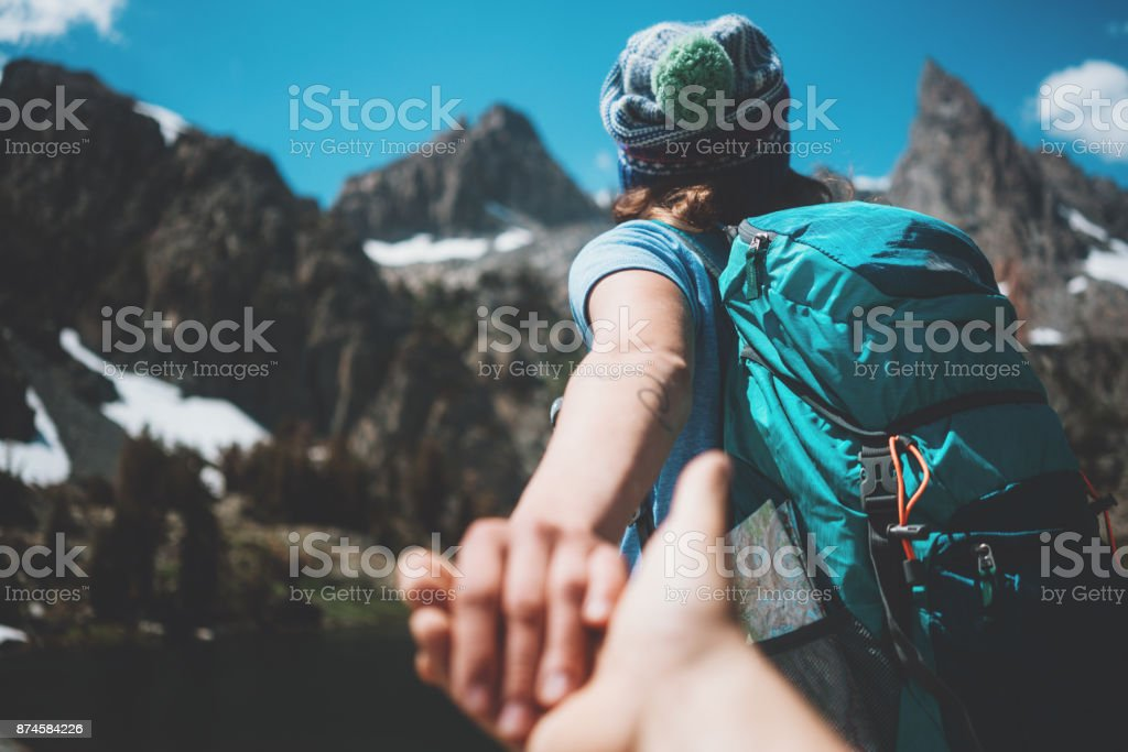 Young active hiking couple with backpacks taking photo, woman guiding...