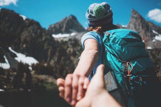 woman leading her friend into the wild by the hand - przewodzić zdjęcia i obrazy z banku zdjęć