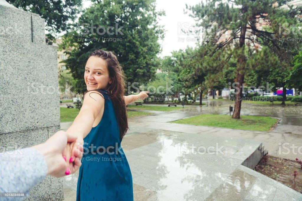 Girlfriend holds hand of her boyfriend, leading him forward