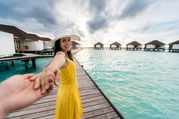 Woman leading man to exploring Young caucasian beautiful woman holding her man for hand and leading him to exploring Maldives. POV concept. romance stock pictures, royalty-free photos & images