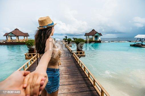 Young slim caucasian woman leading man on pier to beach hut on Maldives. POV. Follow me concept.
