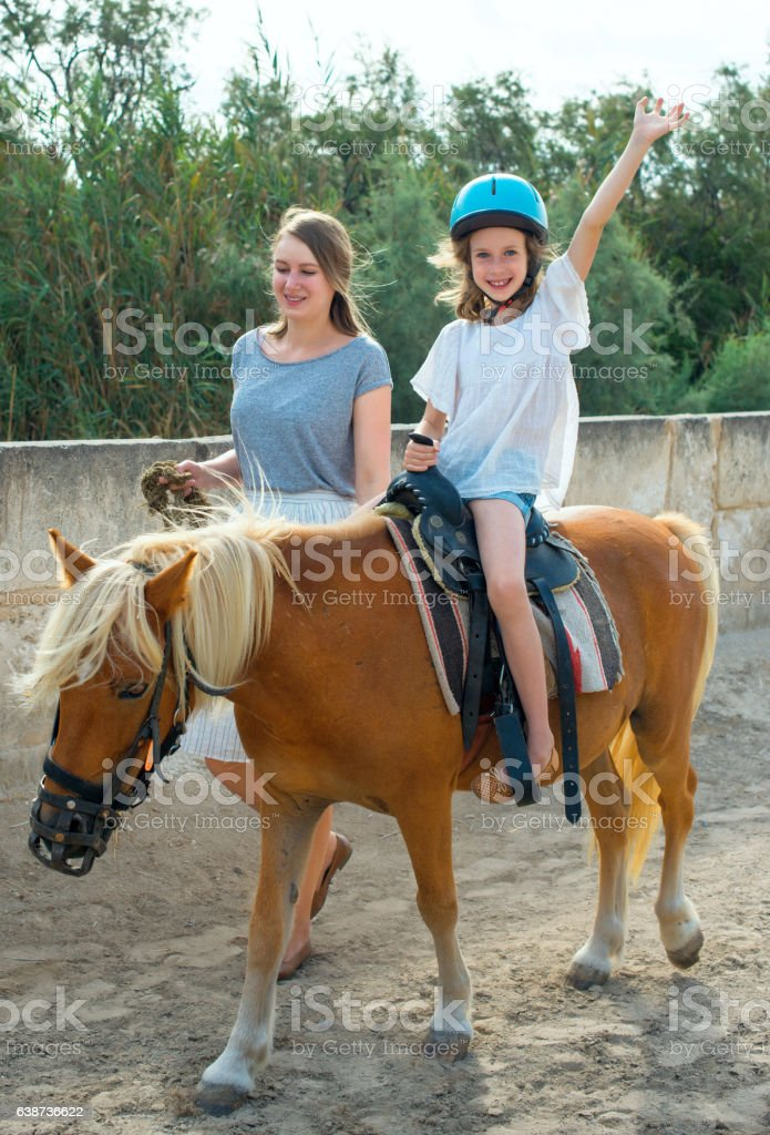 Woman leading pony with little girl. stock photo