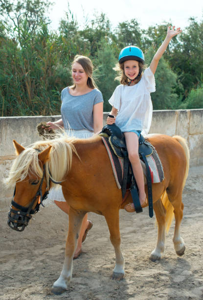 Woman leading pony with little girl. Woman leading pony with little girl. pony stock pictures, royalty-free photos & images
