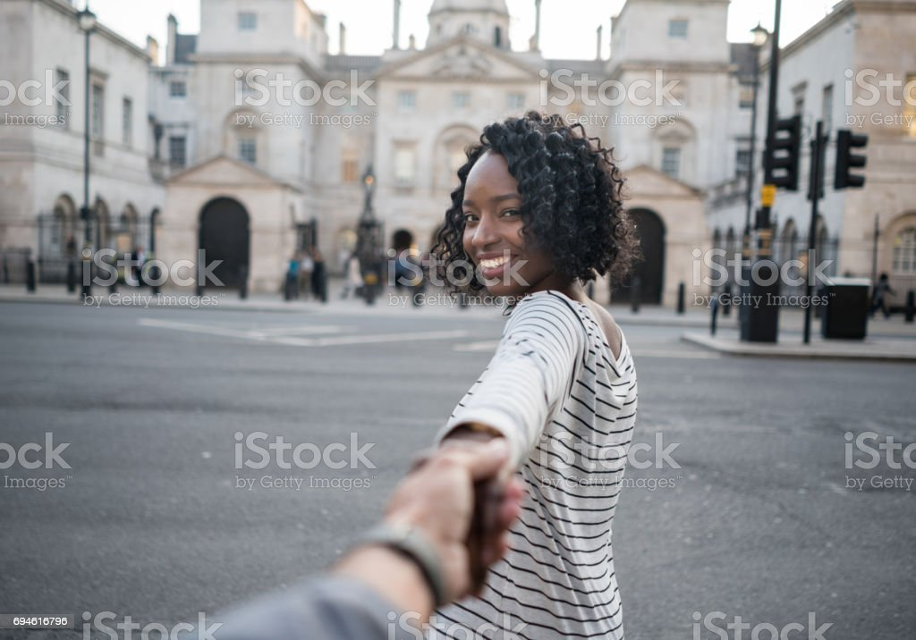 Woman leading the way while traveling in London stock photo