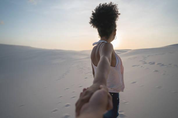 woman leading the way while traveling in the desert - przewodzić zdjęcia i obrazy z banku zdjęć