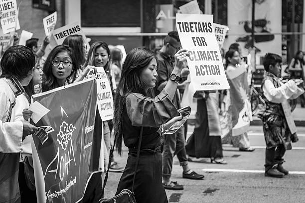Woman leads Tibetan group during the People's Climate March, NYC stock photo