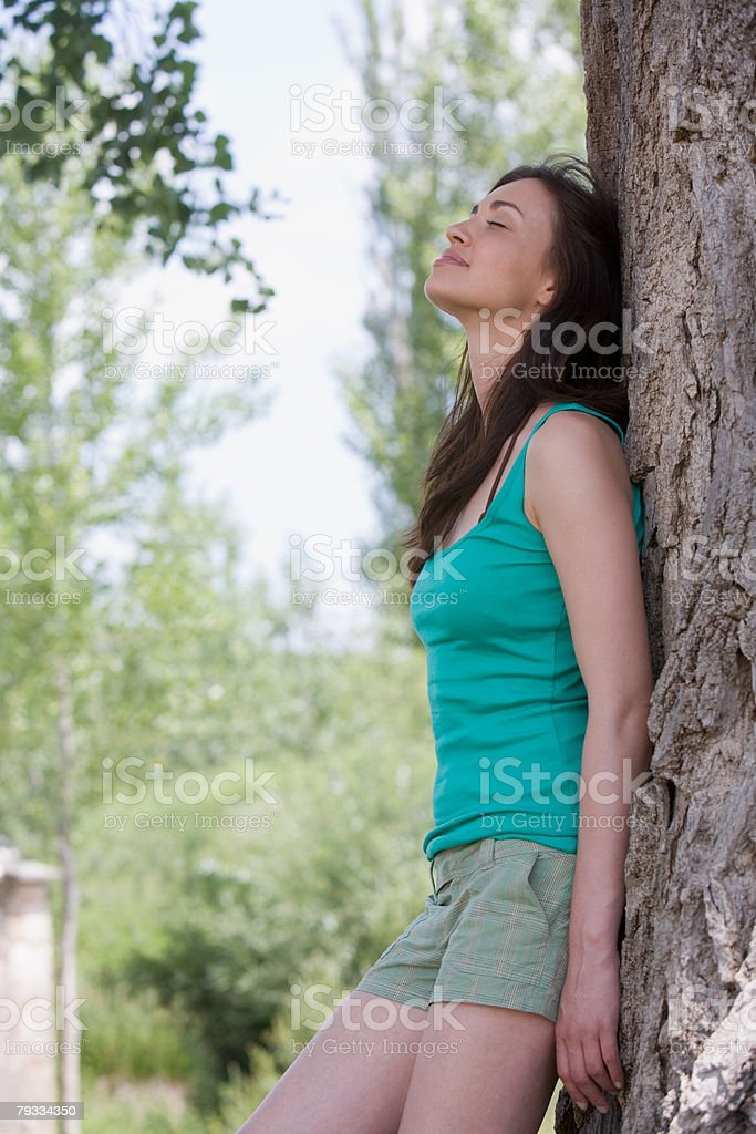 Woman leaning against a tree royalty-free stock photo