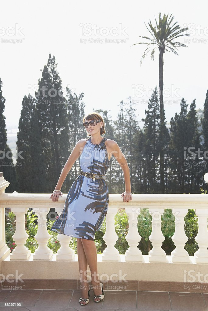 Woman leaning against balcony railing royalty-free stock photo