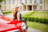 Woman leaning against red retro car