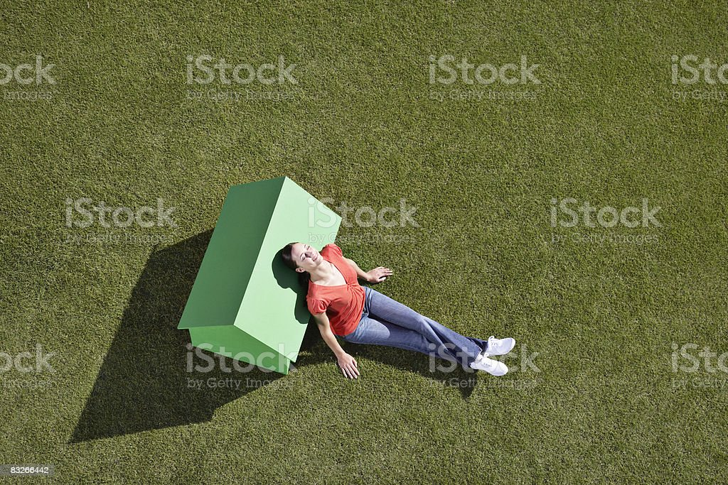 Woman leaning against small model house stock photo