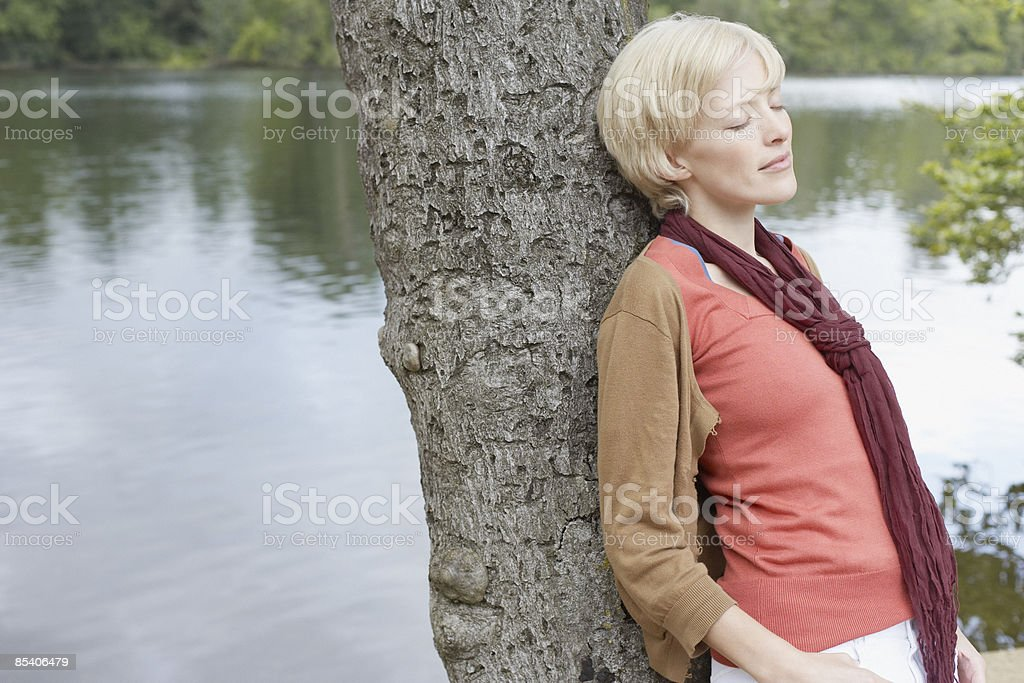 Woman leaning against tree royalty-free stock photo
