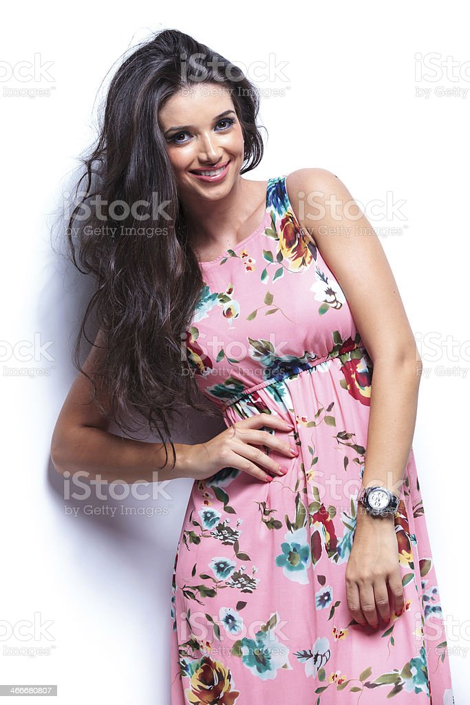 woman leaning against white wall and posing stock photo