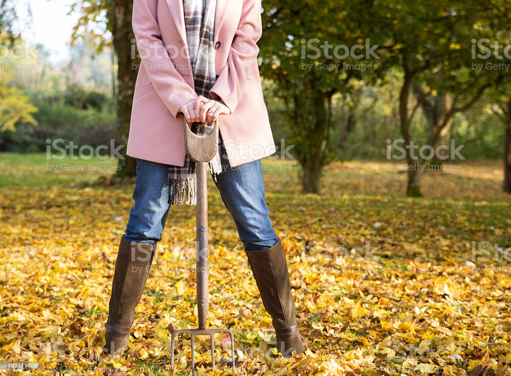 Woman leaning on a garden fork in an autumn scene stock photo