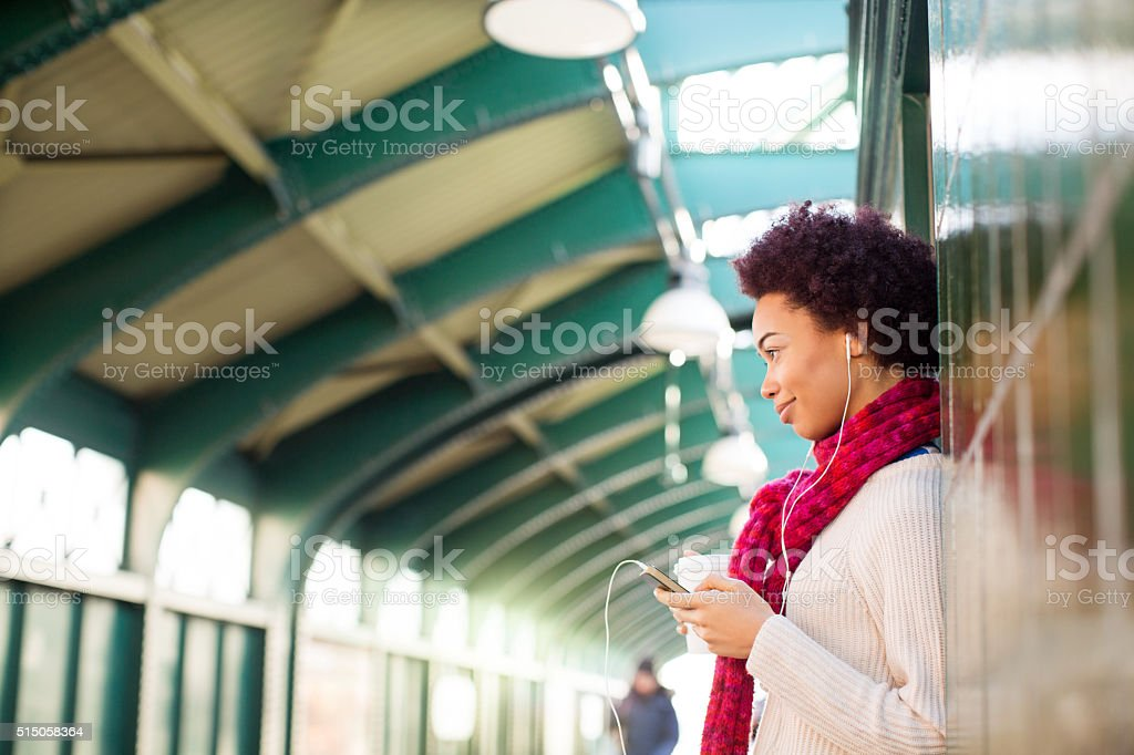 Woman leaning on a wall waiting for the train stock photo