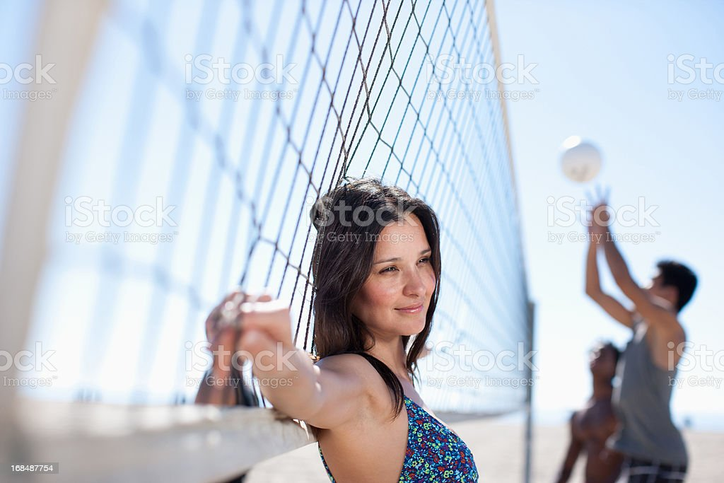 Woman leaning on beach volleyball net royalty-free stock photo