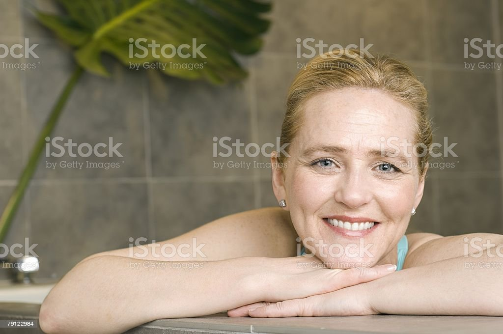 Woman leaning on edge of hot tub 免版稅 stock photo