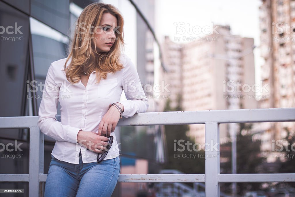 Woman leaning on metal fence photo libre de droits