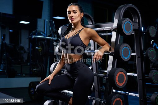 istock Woman leaning on stand with barbells. 1204834481