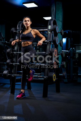 istock Woman leaning on stand with barbells. 1204834494