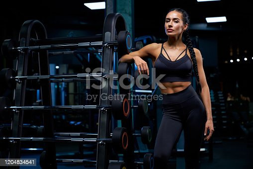 istock Woman leaning on stand with barbells. 1204834541