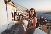 istock Woman leaning on the wall, while exploring streets of Santorini in the evening 1282216059