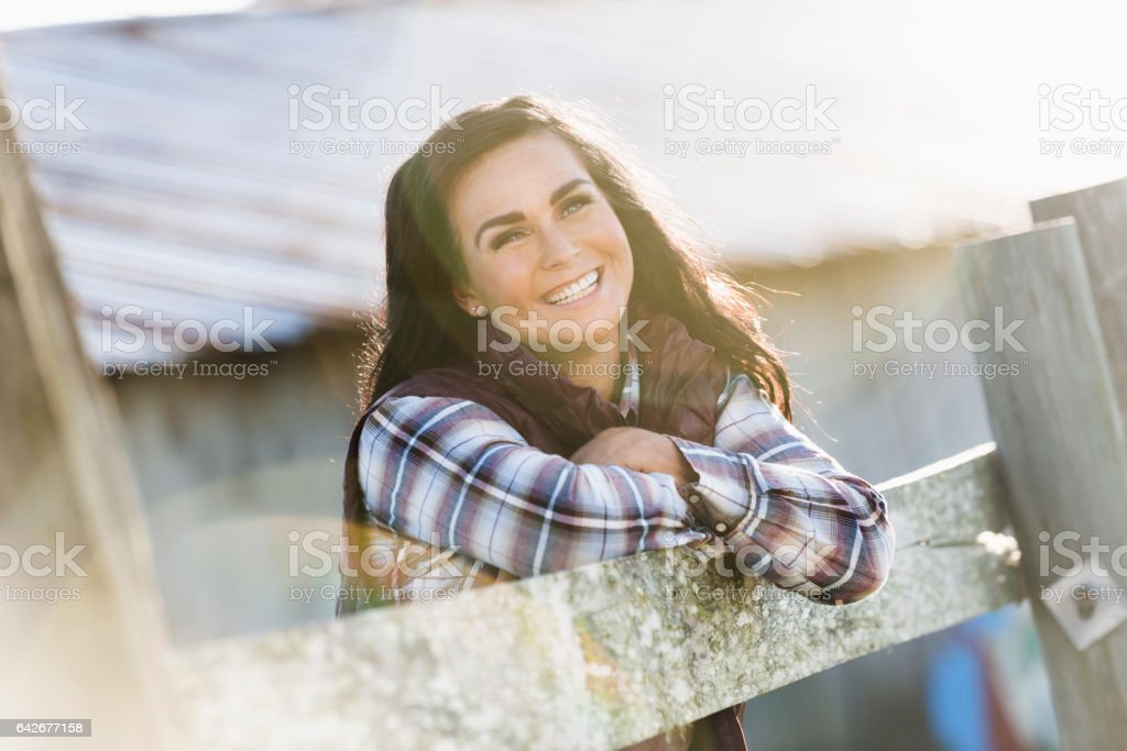 Femme s'appuyant sur une clôture en bois à l'extérieur du bâtiment de la ferme - Photo