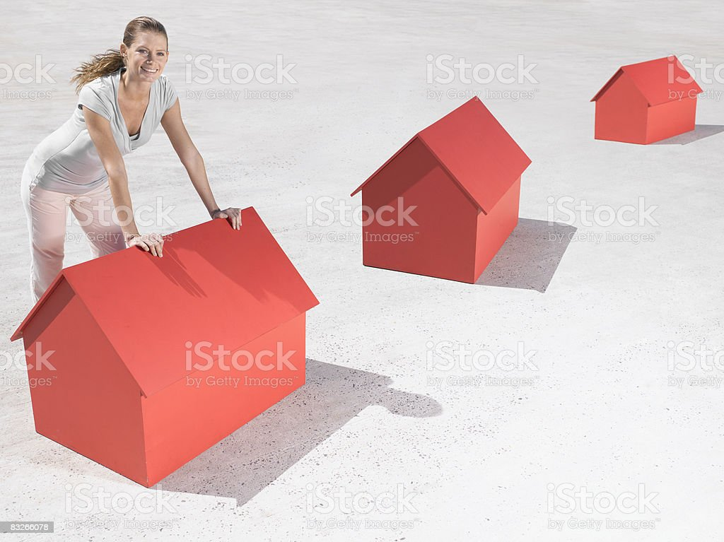 Woman leaning over model houses royalty free stockfoto