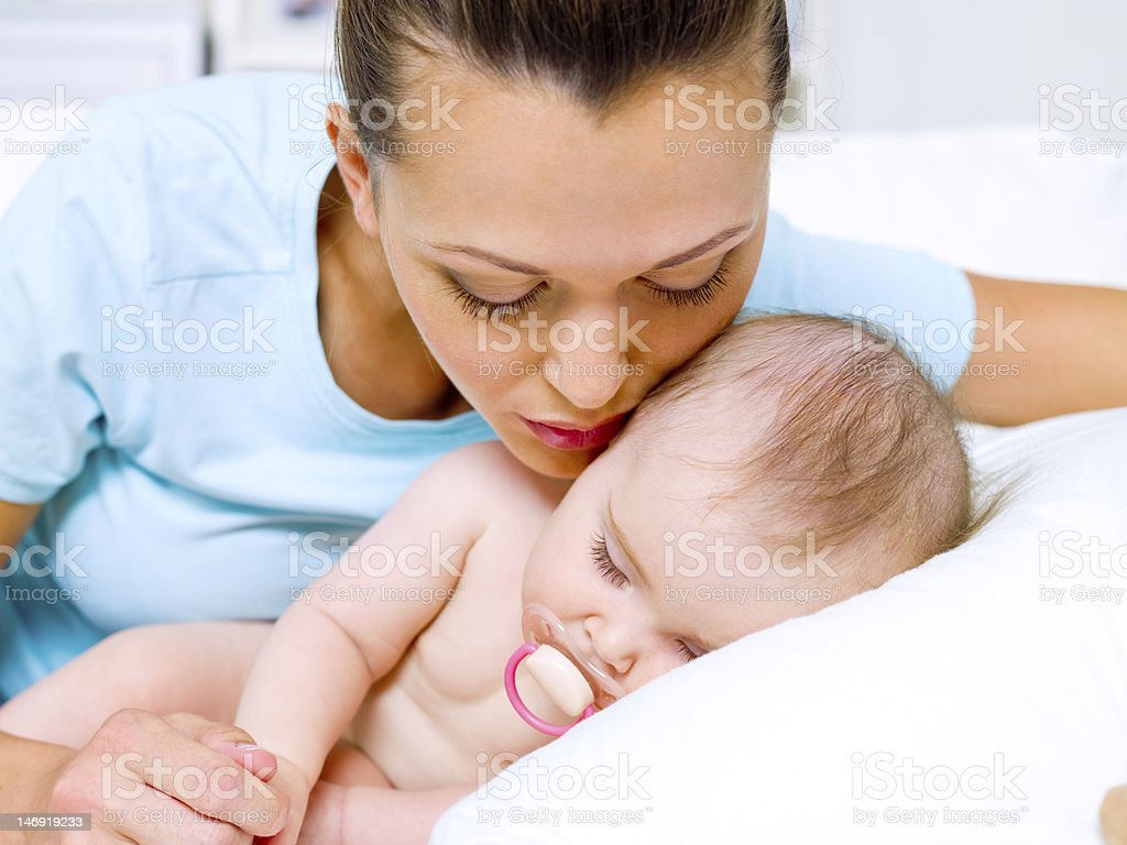 Woman leaning over to kiss sleeping baby royalty-free stock photo