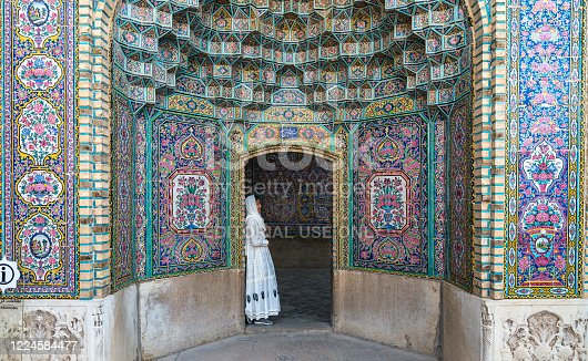 Iran, Shiraz - May 2019: Nasir al-Mulk Mosque with colorful tiles and a tourist leaning at the gate