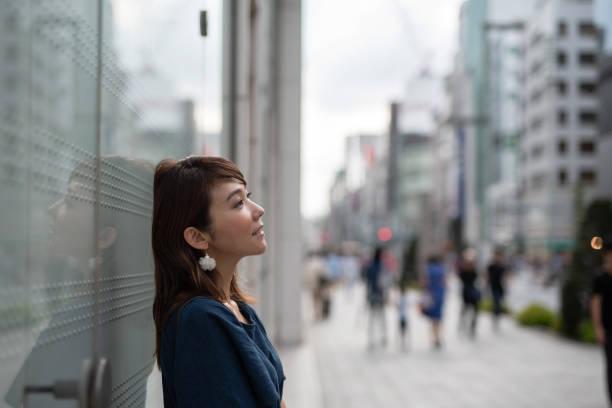 女性ショッピング エリアで壁にもたれて - 女性 横顔 日本人 ストックフォトと画像