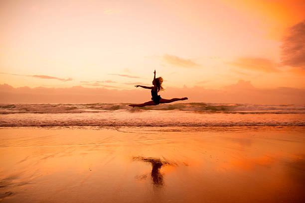 Woman leaping across the sea shore stock photo