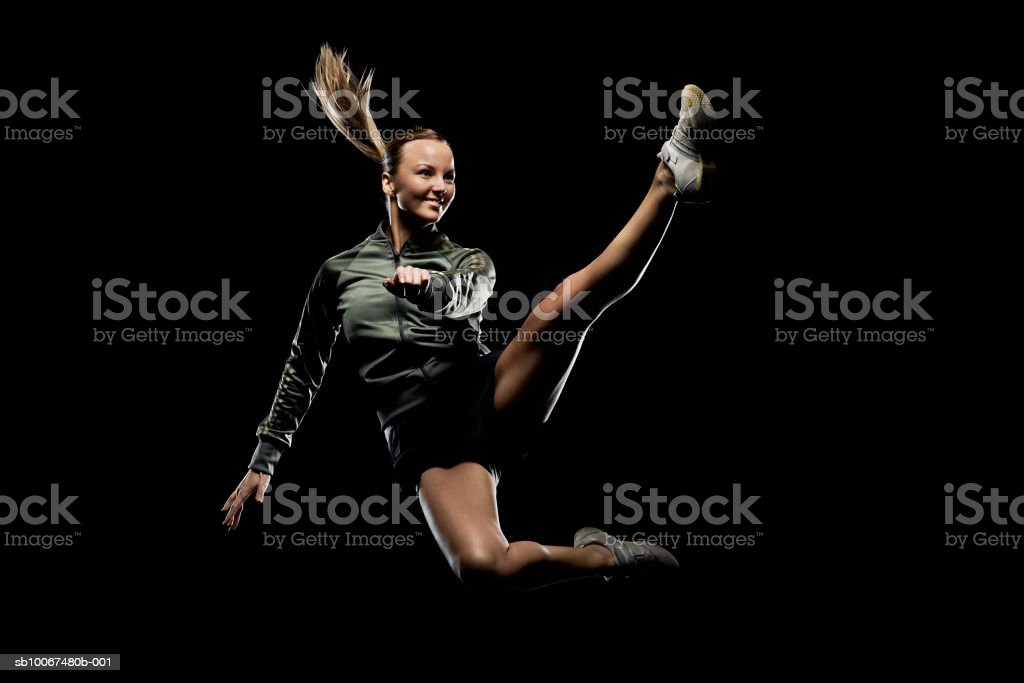 Woman leaping against black background, smiling foto de stock royalty-free