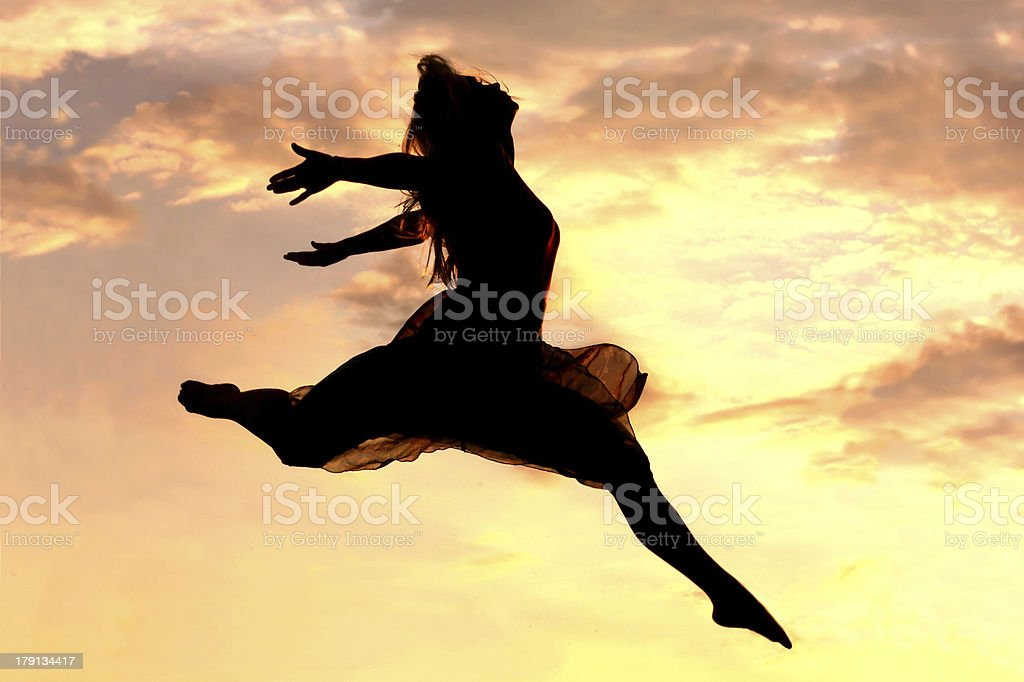 Woman Leaping at Sunset stock photo