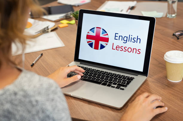 Woman learning english online Mature woman learning English online with computer at office. Laptop screen of woman displaying english lessons poster with British flag. Closeup of student using laptop doing online course on english. english language stock pictures, royalty-free photos & images