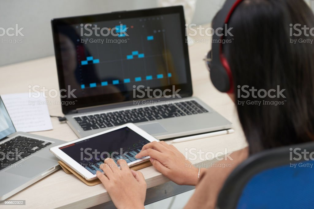 Woman Learning To Play Piano Using Gadgets Stock Photo - Download