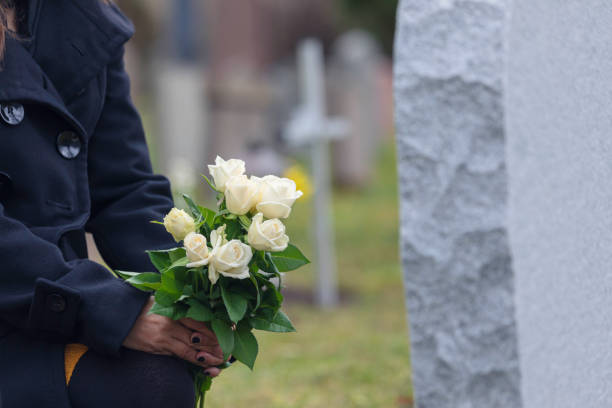 Woman leaving flowers at a grave stock photo