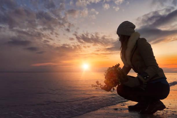 frau verlassen blumen zum meer bei sonnenuntergang am strand - abschiedswünsche stock-fotos und bilder