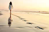Full length of woman walking on wet sea shore at sunset. Female in sundress is leaving her footprints on sand. Rear view of woman spending strolling on idyllic beach.